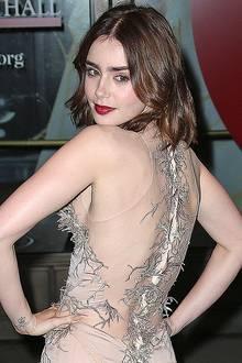 Lily Collins stellt in einem nudefarbenen Kleid mit durchsichtigem Rücken und Korallen-Stickerei ihren subtilen Sexappeal unter Beweis.