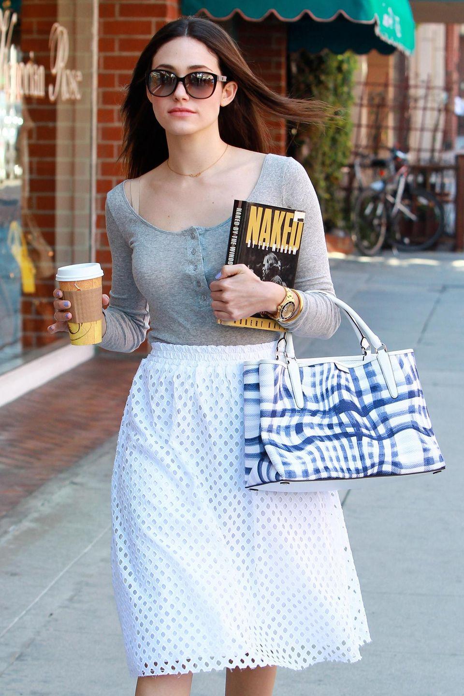 """Emmy Rossum ist auf dem Weg ins Nagelstudio und um die Wartezeit zum Lesen zu nutzen hat sie sich das Buch """"Naked By The Window"""" von Robert Katz mitgebracht."""