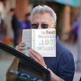 """Nach seinem Arztbesuch versteckt sich Dustin Hoffman vor den Paparazzis hinter seinem Buch """"The Best Things To Do In Los Angeles - 1001 Ideas""""."""