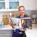 """Bewaffnet mit einem Holzlöffel und einem ehrgeizigen Blick, möchte Reese Witherspoon einige Rezepte aus dem Kochbuch von Freundin und Kollegin Gwyneth Paltrow """"It's All Easy"""" nachkochen. Sie hat jüngst ein Kochbuch mit Alltagsgerichten für die ganz schnelle Küche herausgebracht."""
