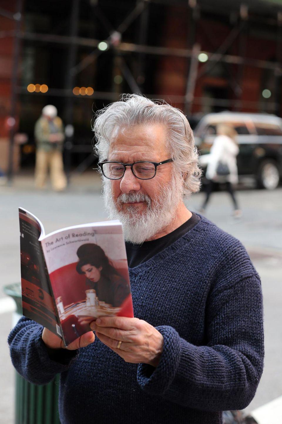 """Dustin Hoffman ist so sehr in ein Buch versunken, dass er sogar unterwegs auf den Straßen von New York blättern muss. Es handelt sich um den Bildband """"The Art of Reading"""" von Fotograf Lawrence Schwartzwald."""