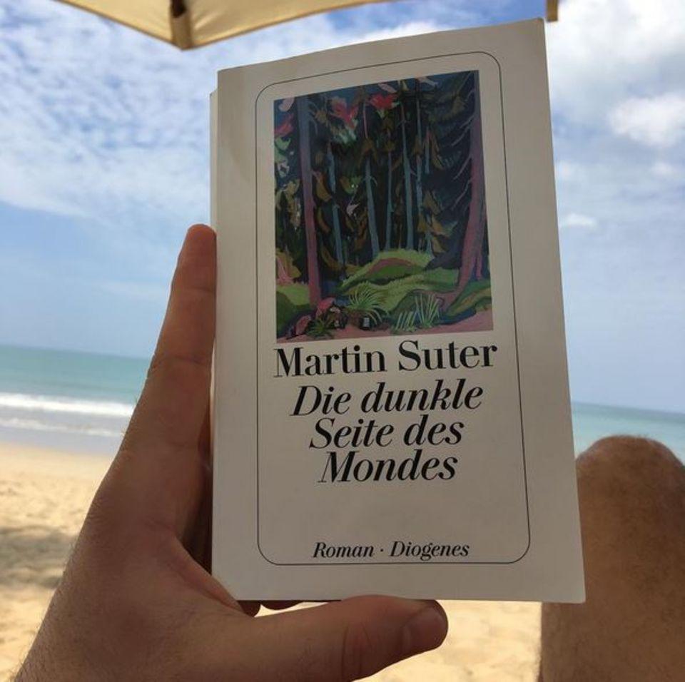 """Unter der Sonne liest Elyas M'Barek das Buch """"Die dunkle Seite des Mondes"""" von Martin Suter und spricht eine deutliche Empfehlung aus."""