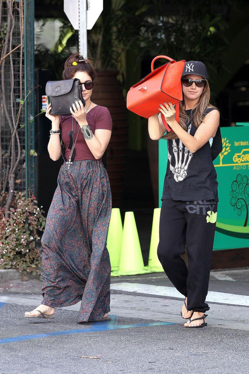 Die Lösung verrät dieses Bild, auf dem Vanessa Hudgens und Ashley Tisdale zwar auch versuchen, sich zu verstecken. Ihre Handtaschen sind dabei aber längst nicht so effektive Hilfsmittel.