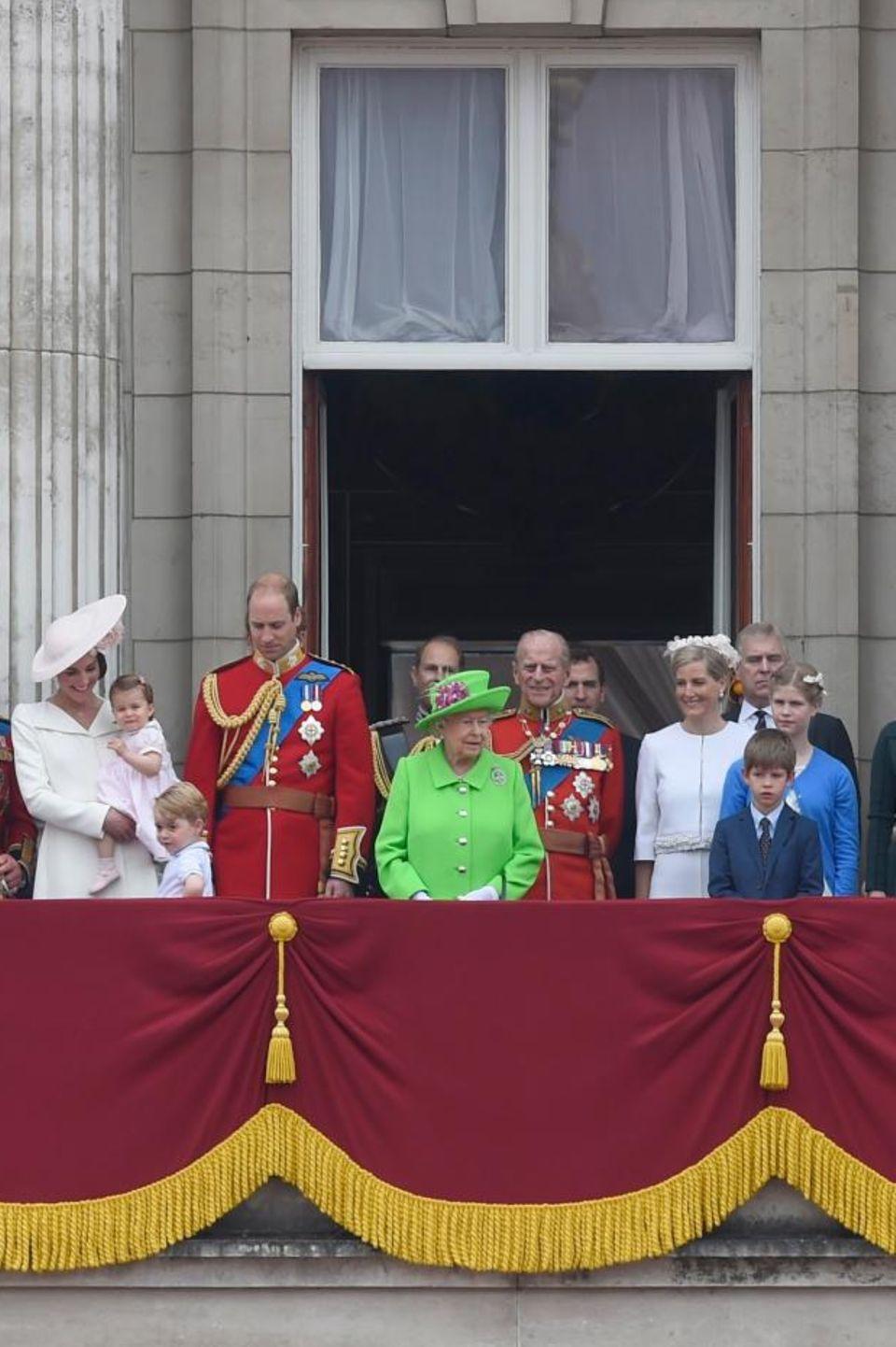 """11. Juni 2016  Selten sieht man so viele Windsors gemeinsam wie bei der Balkonszene bei """"Trooping the Colour"""". Neben der Queen (in grün) stehen links Prinz William und rechts Prinz Philip in roter Uniform. Neben William zu sehen sind Herzogin Catherine (mit Prinzessin Charlotte auf dem Arm), Prinz Charles und Herzogin Camilla, Prinzessin Anne (un Uniform), Zara Phillips und ihr Mann Mike Tindall. Rechts von Prinz Philip: Gräfin Sophie, Prinz Andrew, Lady Louise, James Viscount Severn und Prinzessin Eugenie."""