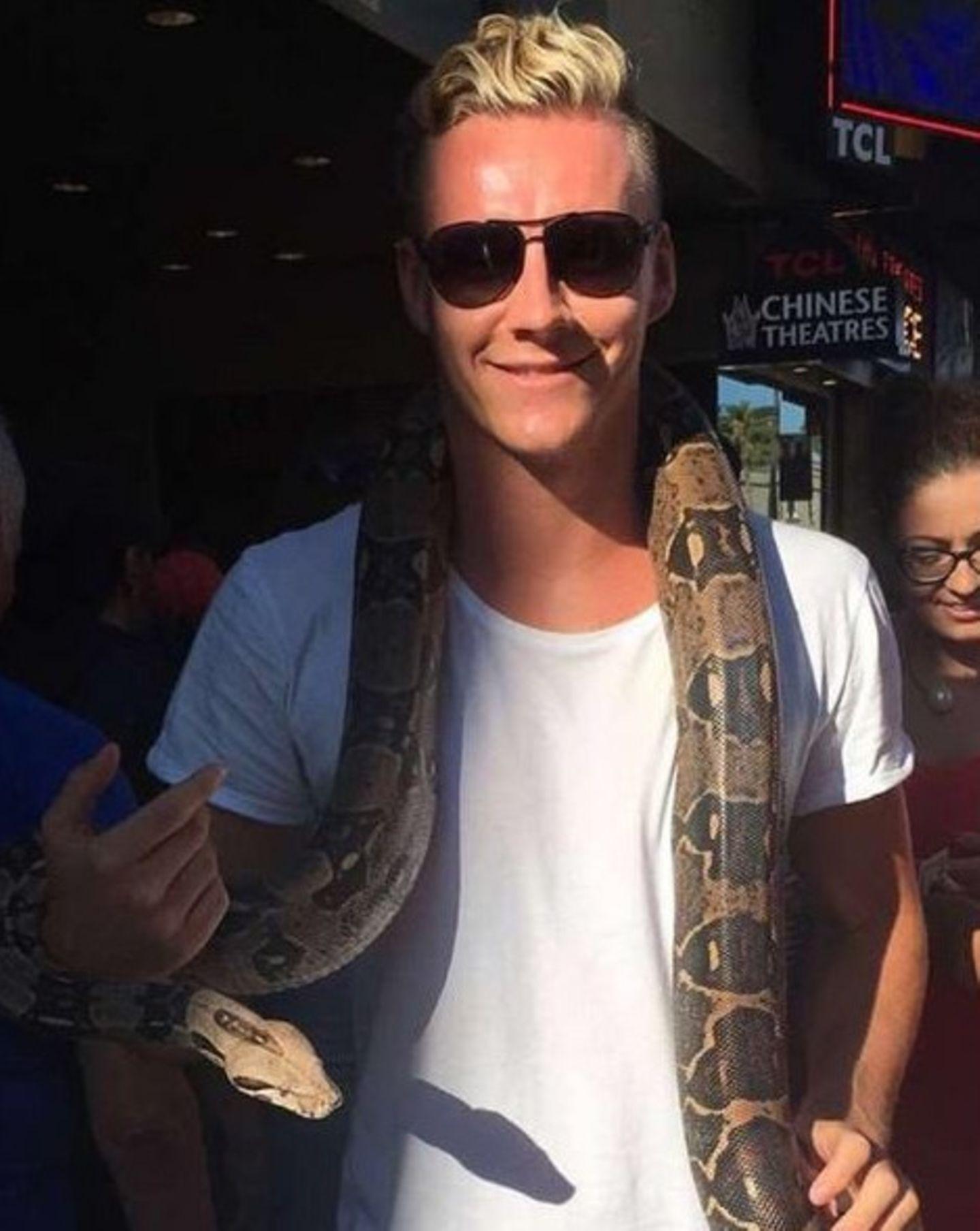 """Ganz gewöhnlich über den """"Hollywood Walk of Fame"""" spazieren? Für Bernd Leno viel zu langweilig! Beim Sternchenschauen hängt der Torwart sich lieber noch eine riesige Schlange um den Hals."""