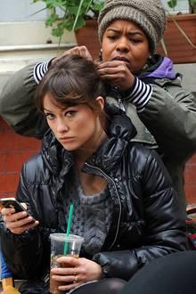 Während Olivia Wilde am Set von der Stylistin bearbeitet wird, beschäftigt sich die Schauspielerin mit ihrem iPhone.