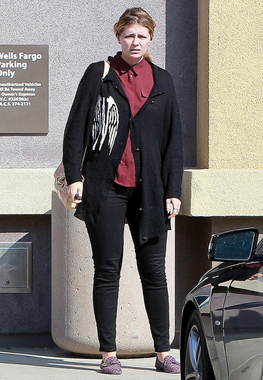 Mit zugeknöpfter, bordeauxroter Bluse und abgetragener Strickjacke wirkt Mischa Barton selbst nicht ganz glücklich.