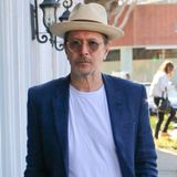 Sommerlich-maritim mit weißen Jeans, T-Shirt, blauem Sakko und Bast-Fedora zieht Gary Oldman durch die Nachbarschaft von West Hollywood.