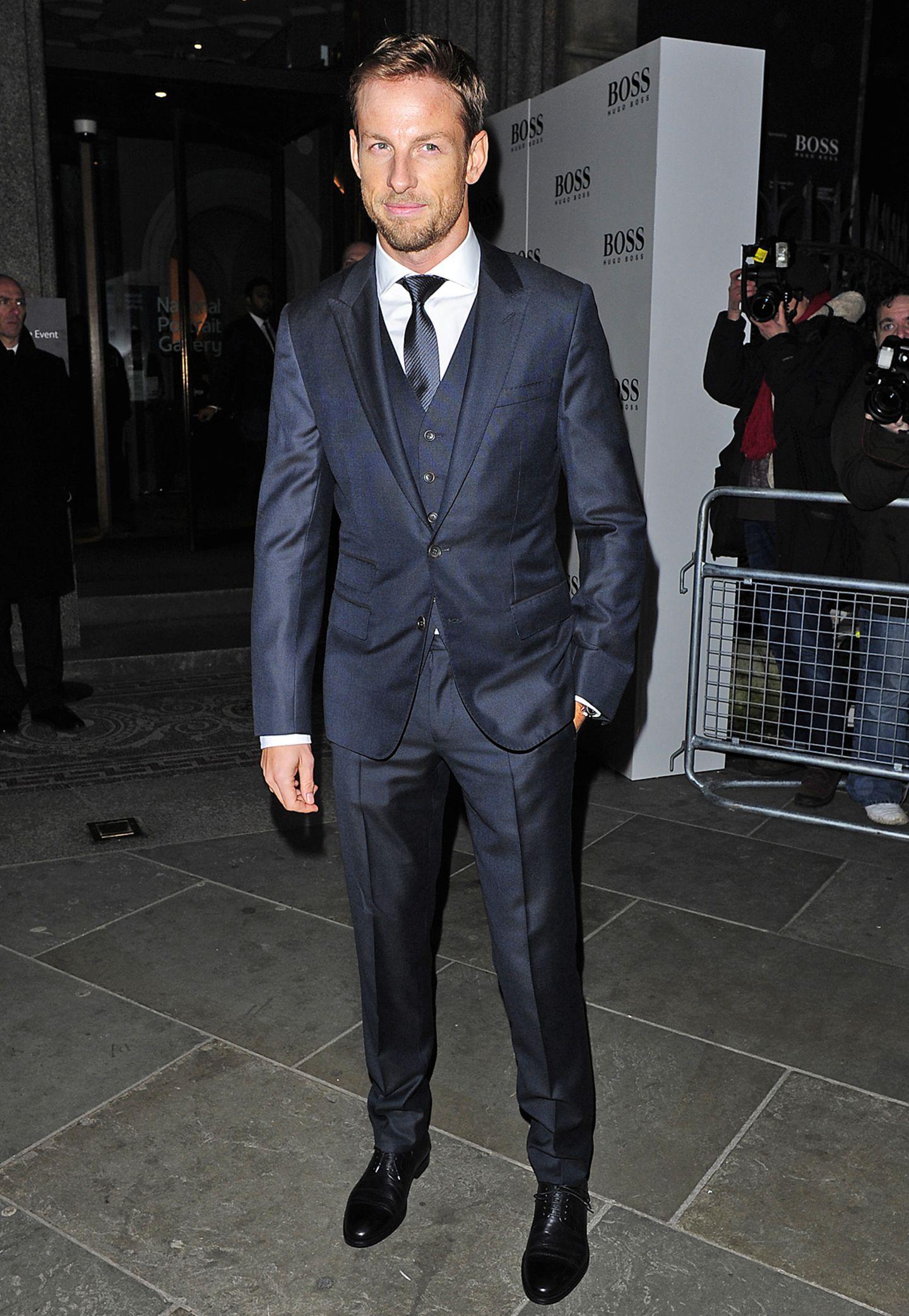 Formel-1-Pilot Jenson Button besucht im eleganten Dreiteiler eine Ausstellungseröffnung in London. Durch den schimmernden, nachtblauen Stoff wirkt der Look sehr modern.