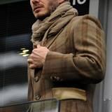 David Beckham guckt sich ein Fußbhallspiel nicht in bequemen Freizeitklamotten an, sondern sieht aus als wäre er direkt von eine