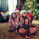 Jessica Alba postet ein Weihnachtsbild mit ihrem Mann Cash Warren und den beiden Töchtern Honor und Haven. Im Hintergrund sind der geschmückte Tannenbaum und eine große Geschenketüte zu sehen.
