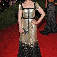Im Kontrast zu ihrem düsteren Augen-Make-up wirkt das gold-schwarze Kleid von Tory Burch an der zierlichen Schauspielerin sehr feminin und edel.