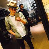 Brooklyn Beckham probiert in einem Laden verschiedene Hüte auf und wird dabei von Papa David Beckham gestört, der ihm durch das Bild läuft.