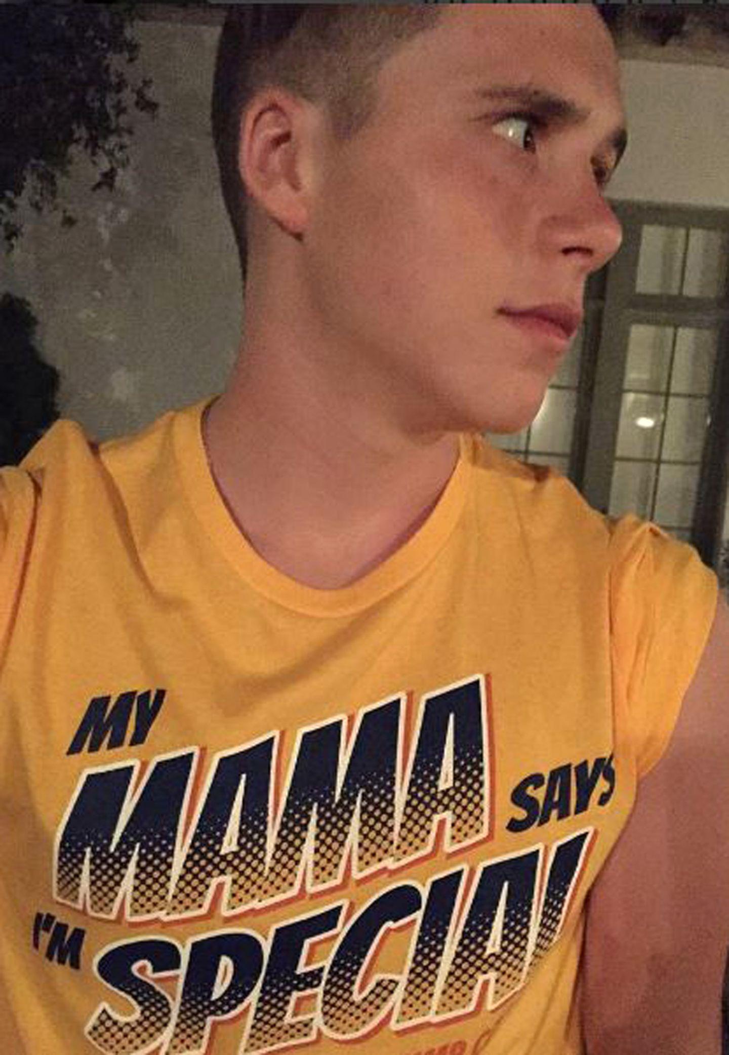 """So richtig begeistert scheint Brooklyn Beckham von seinem Slogan-Shirt nicht zu sein. """"Mama sagt, ich bin besonders"""" steht auf dem gelben Oberteil, das ihm ganz offensichtlich die stolze Mutter Victoria Beckham geschenkt hat."""