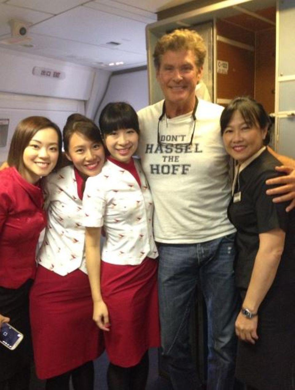 """David Hasselhoff lächelt mit den Stewardessen auf seinem Flug nach Bali in die Kamera und verkündet auf seinem Shirt """"Don't Hassell The Hoff""""."""