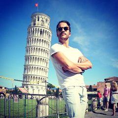 Ganz schön lässig! Kostja Ullmann lehnt sich an den schiefen Turm von Pisa. Er ist gerade in Italien unterwegs und teilt seine Erlebnisse mit seinen Twitter-Fans.