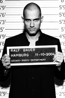 Raspelkurzes Haar und verwegener Blick: Ralf Bauer hält sein Schild in die Kamera.