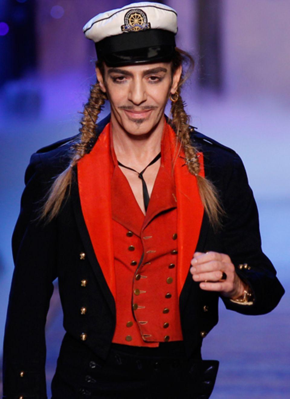 Designer John Galliano zeigt sich nach seiner Show auf dem Laufsteg.