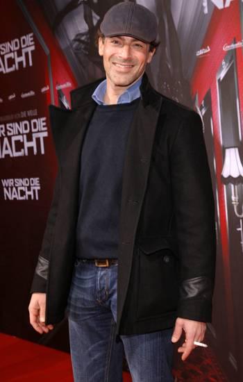 Gedeon Burkhard geht auf der Premierenfeier lässig mit Zigarette über den roten Teppich.
