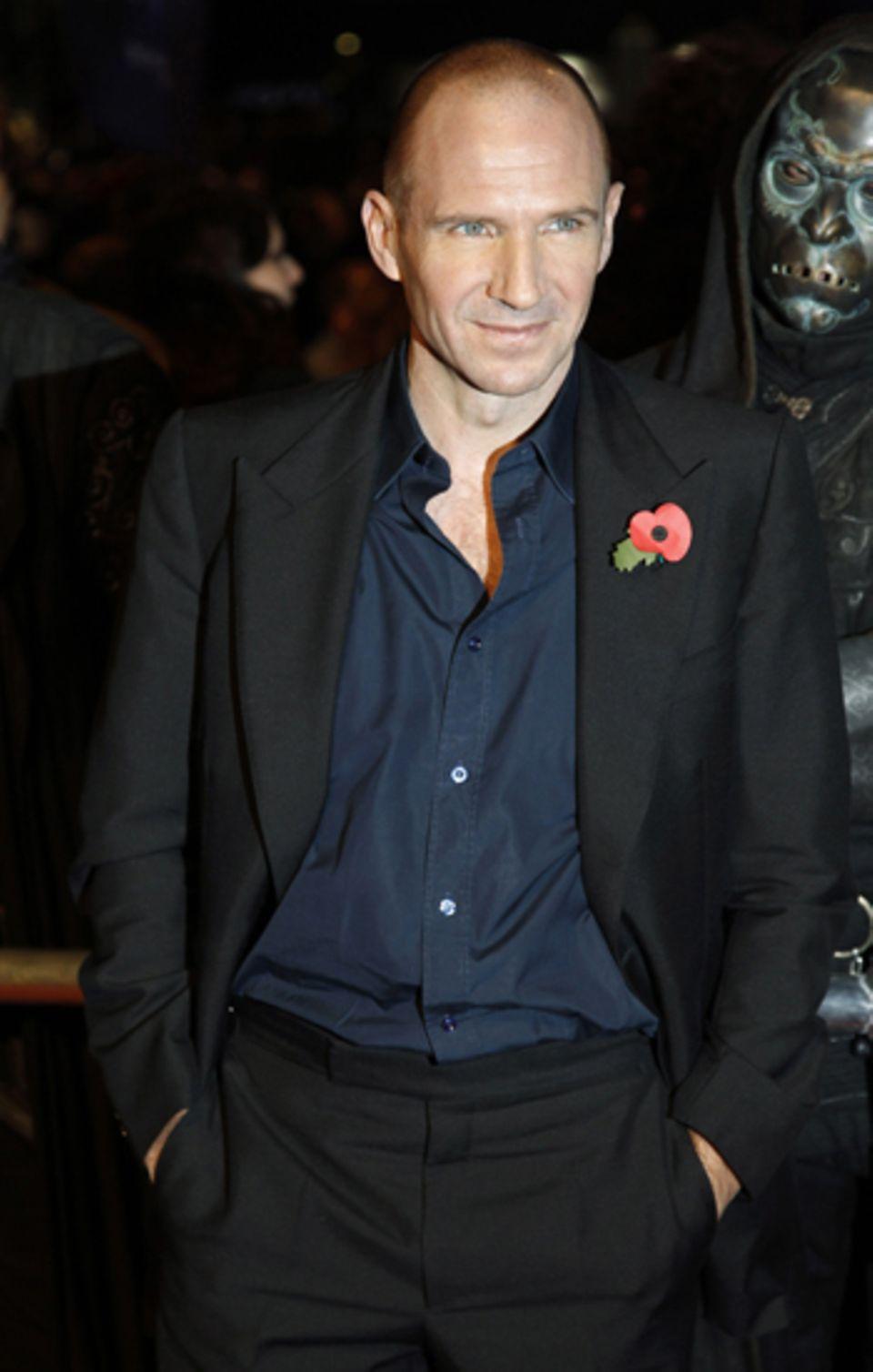 Ralph Fiennes stellt sich lässig mit den Händen in der Hose vor die Kameras.