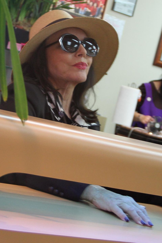 Schauspielerin Joan Collins lässt sich - schick mit Hut und Sonnenbrille- in Beverly Hills die Nägel lackieren.
