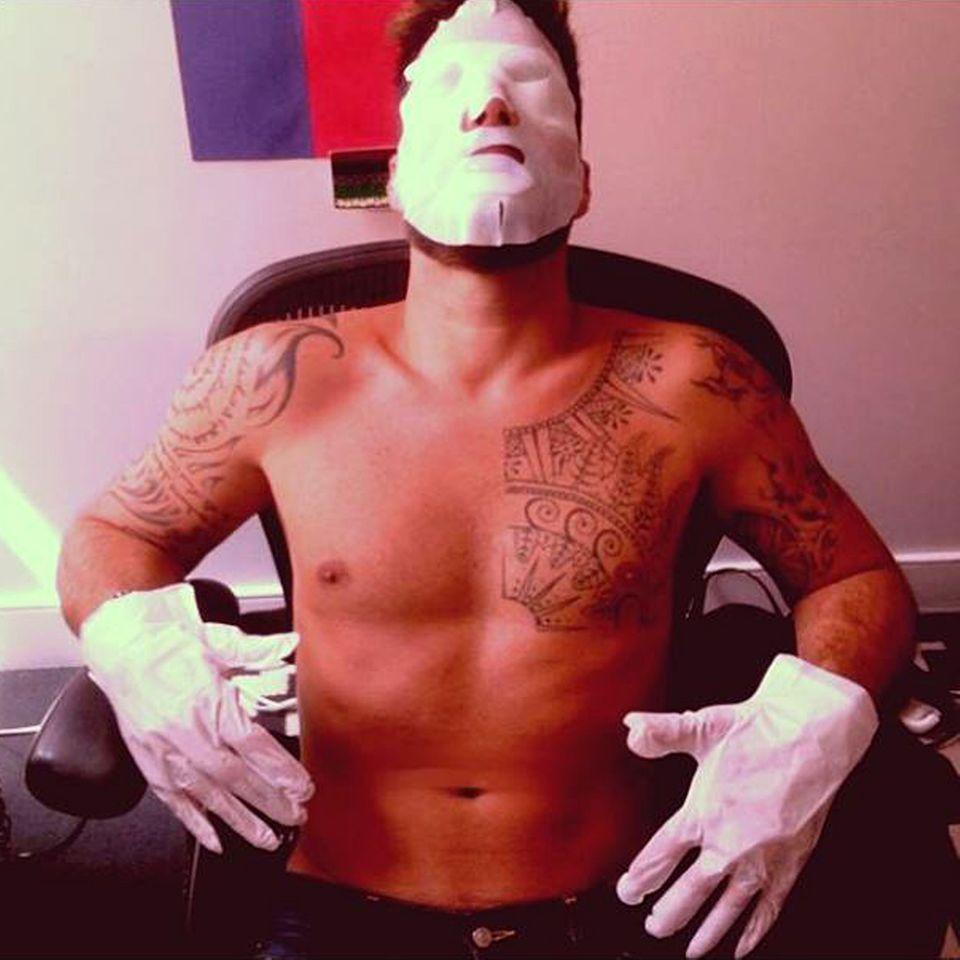 Unter der aufgelegten Gesichtsmaske verbirgt sich der Latino-Schönling Ricky Martin, der sich zur Beauty-Behandlung auch gleichzeitig seine Lippen und Hände maskieren lässt.