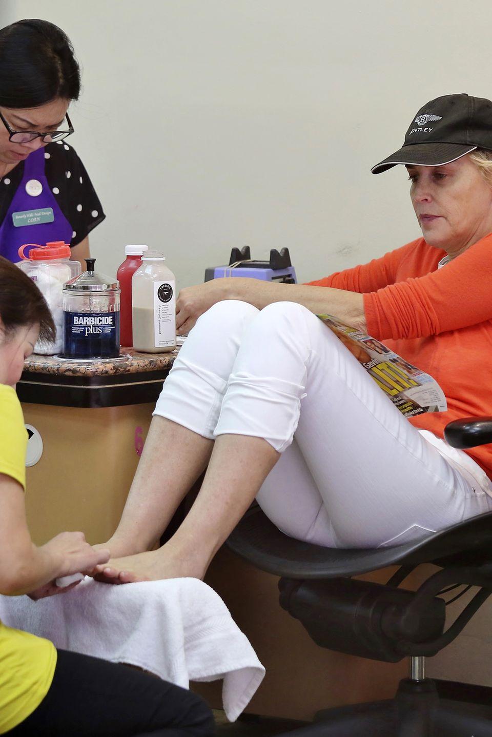 """Einmal Mani und Pedi - aber bitte gleichzeitig! Komplett uneitel lässt sich Sharon Stone bei """"Beverly Hills Nail Design"""" die Nägel machen, trinkt einen Saft und schaut dabei nach, ob sie sich in der Zeitschrift wiederfindet."""