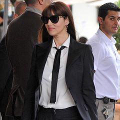 Monica Bellucci schafft durch zwei Accessoires einen perfekten Stilbruch: Zum eleganten, schwarzen Hosenanzug trägt sie eine maskuline Krawatte und ultra-feminine Plateau-Pumps.