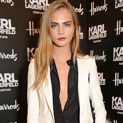 Cool, cooler, Cara: In einem weißen Hosenanzug von Karl Lagerfeld perfektioniert das britische It-Model den lässigen Herren-Chic.