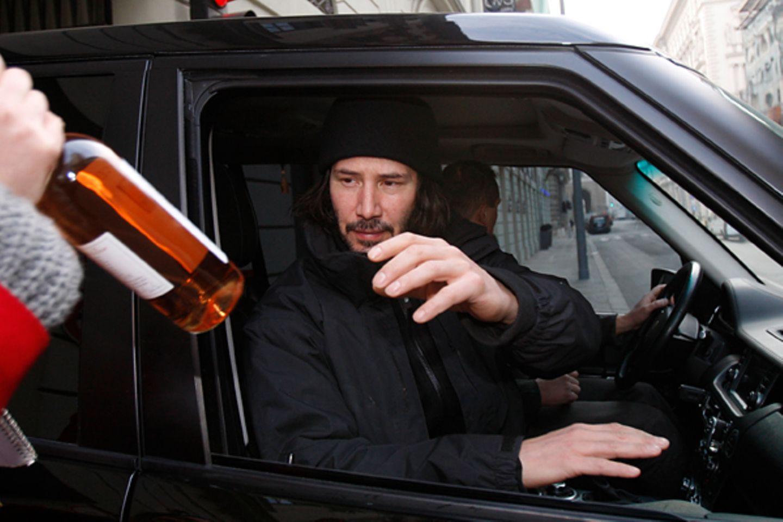 11. März 2011: Keanu Reeves bekommt von einem Fan eine Flasche Wein geschenkt.