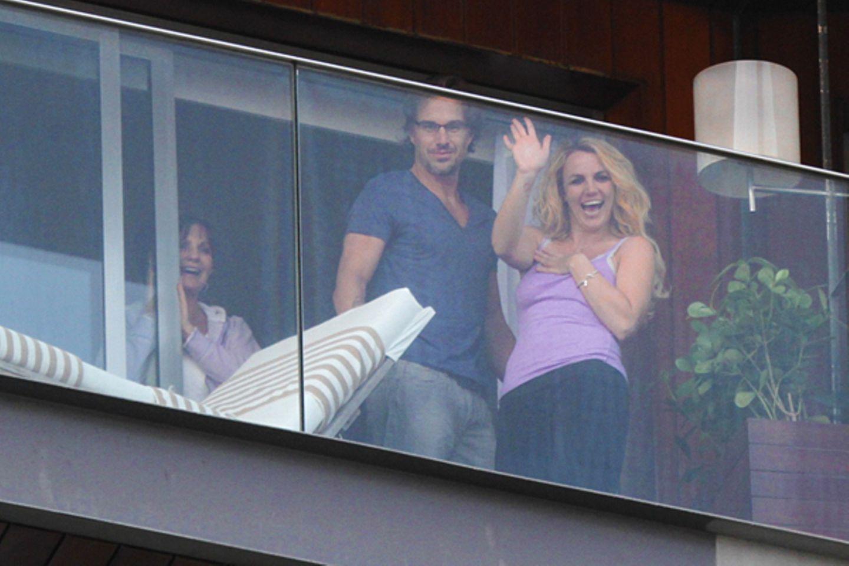 13. November 2011: Überschwinglich winkt Britney Spears vom Balkon eines Hotels in Rio de Janeiro. Jason Trawick schaut hingegen