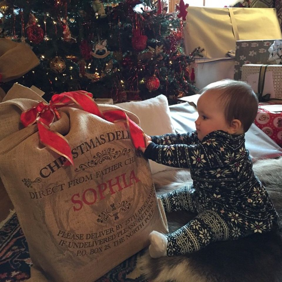 Töchterchen Sophia darf ihr erstes Geschenk unter dem Weihnachtsbaum auspacken. Mama Tamara Ecclestone teilt dieses niedliche Foto auf Instagram.