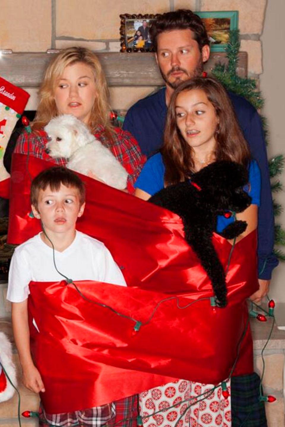 """Kelly Clarkson teilt das Weihnachtsfoto, auf dem sie mit ihrem Ehemann Brandon Blackstock und dessen Kindern Savannah, elf, und Seth, sieben, zu sehen ist, mit ihren Facebook- und Twitterfans. """"Merry Christmas von den Blackstocks"""", schreibt die Sängerin dazu. Das Weihnachtsfest im nächsten Jahr können sie bereits zu fünft verbringen. Die Frischvermählten erwarten ihr erstes gemeinsames Kind."""