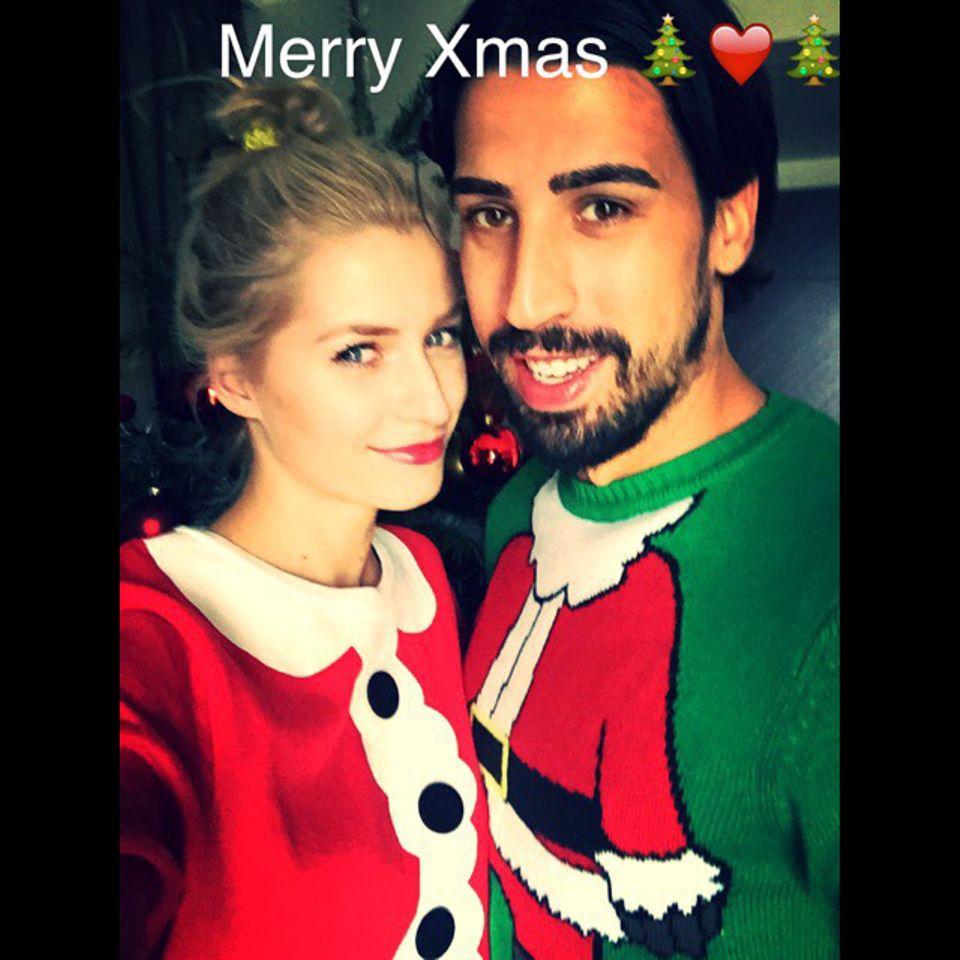 Lena Gercke und Sami Khedira sind voll in Weihnachtsstimmung und posieren im Weihnachtspullover-Partnerlook für ein Foto.