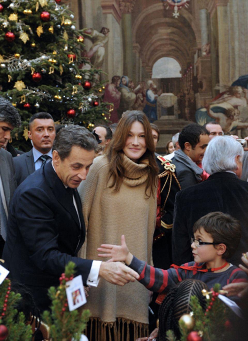 Carla Bruni und Frankreichs Präsident Nicolas Sarkozy verteilen bei einer Weihnachtsfeier im Pariser Élysée-Palast Weihnachtsges