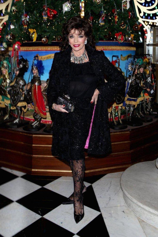 """Joan Collins funkelt im Londoner Luxuskaufhaus """"Claridge's"""" mit dem Baumschmuck um die Wette."""