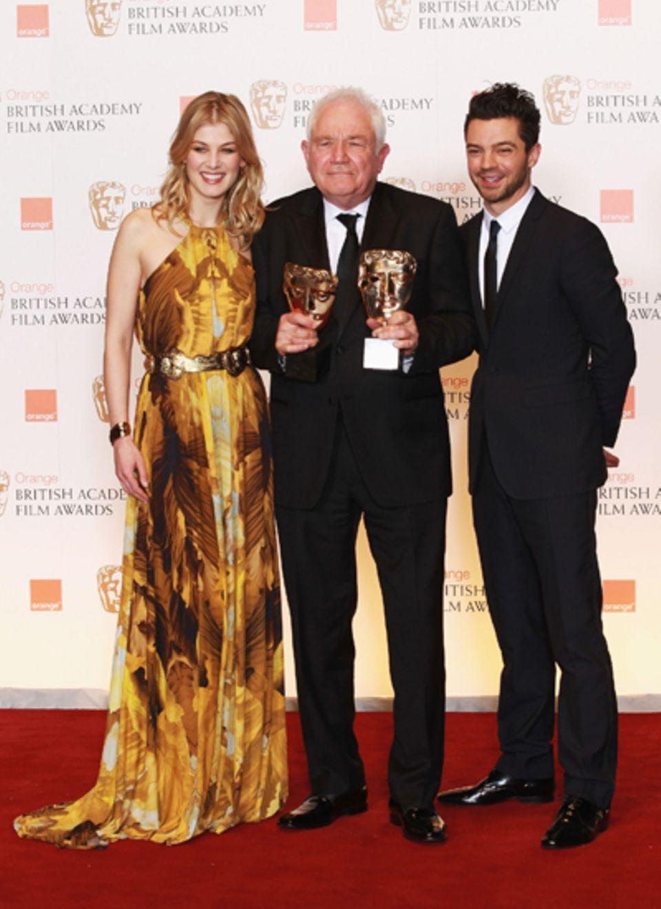 """Rosamund Pike und Dominic Cooper nehmen David Seidler in die Mitte, der sich über Auszeichnungen für """"The King's Speech"""" freuen"""