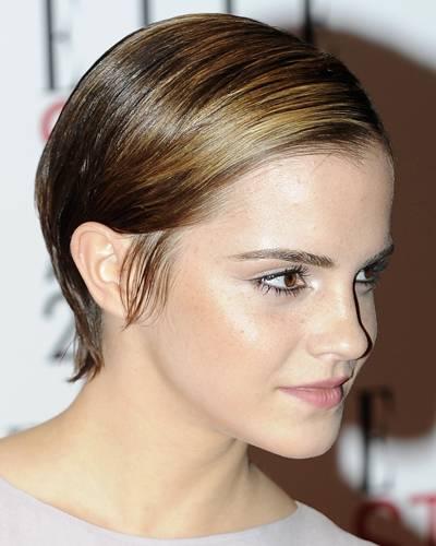 Emma Watson trägt einen streng zur Seite gekämmten Kurzhaarschnitt. Der extreme Glanz lässt ihre Frisur noch moderner wirken.