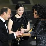 """Oprah Winfrey überreicht den Oscar an Charles Ferguson und Audrey Marrs für ihren Dokumentarfilm """"Inside Job""""."""