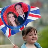 Ein kleines Mädchen schwingt eine Fahne mit einem Bild des Traumpaares.