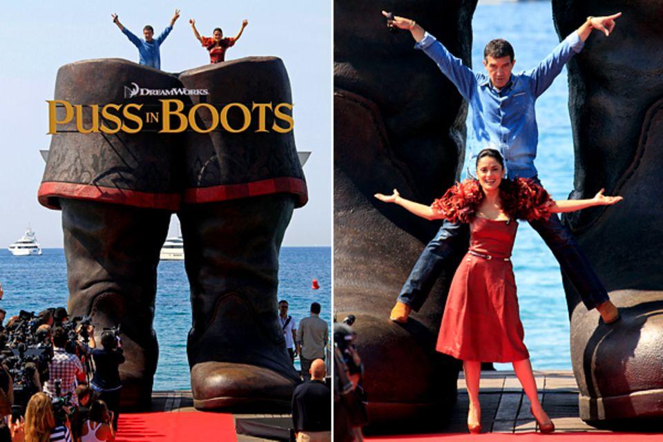"""Filmfestival Cannes: Antonio Banderas und Salma Hayek posieren in Anlehnung an ihren Film """"Puss in Boots"""" mit einem Paar riesige"""