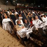 Filmfestival Cannes: Gespannt warten die Zuschauer auf den Beginn einer Kinovorführung in gemütlicher Strandatmosphäre.