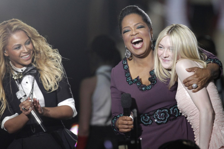 Die Stimmung könnte besser nicht sein: Freudestrahlend nimmt Oprah Winfrey Dakota Fanning in ihren Arm.