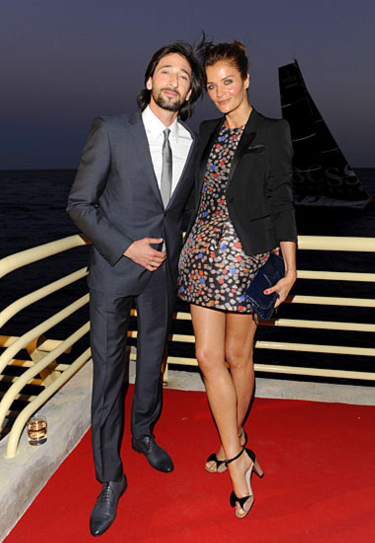 Adrien Brody und Helena Christensen, beide in BOSS Black, lassen sich auf der Terrasse der Villa Key Largo den abendlichen Somme