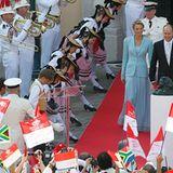 Fürst Albert und Fürstin Charlene kommen in den Innenhof des Palastes, wo zahlreiche Gäste und Würdenträger auf sie warten.