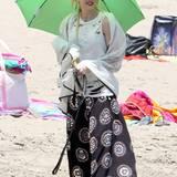 Oben schützt der Sonnenschirm, unten der bodenlange Maxirock im Indianer-Look Gwen Stefani vor der Sonneneinstrahlung.