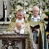 Vorsichtig hält der Erzbischof die kleine Prinzessin über das silberne Taufbecken. Rundherum strahlende Gesichter.