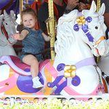 In einem gemütlichen Denim-Jumpsuit dreht Harper glücklich ihre Runden auf dem Karussel in Disneyland und winkt verträumt.