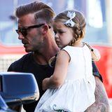 Ganz müde von der Reise, aber bezaubernd gestylt mit Zöpfen, Schleifchem im Haar und einem schön bestickten, weißen Sommerkleid ruht sicher Harper am Flughafen von L.A. auf Papa David Beckhams Arm aus.