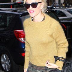 Gwen Stefani in einem senfgelben Flauschepulli. Die Sängerin kombiniert ihn ganz lässig mit einer Military-Hose.